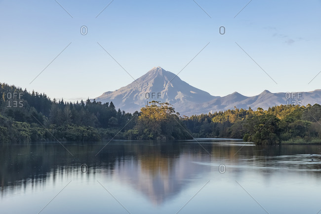 New Zealand- Scenic view of forest surrounding Lake Mangamahoe with Mount Taranaki looming in background
