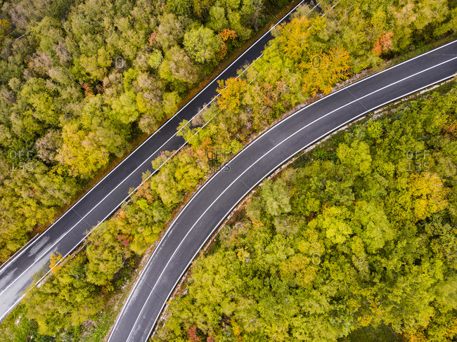 Italy- Trentino- Trento- Aerial view of empty highway stretching across autumn forest in European Alps