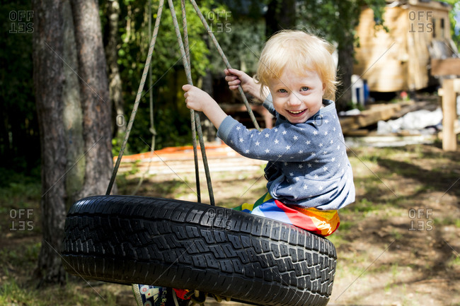 Portrait of happy toddler girl sitting on tire swing