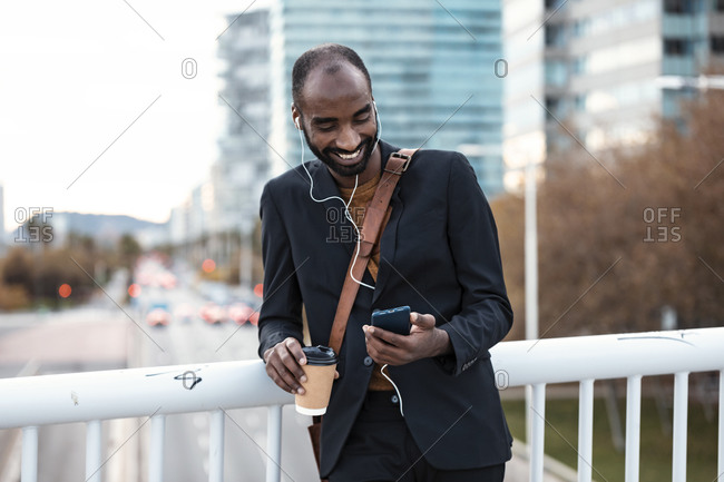 Smiling young businessman with coffee to go listening music with earphones and smartphone
