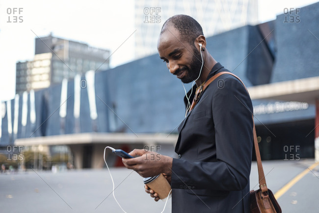 Portrait of smiling young businessman with coffee to go listening music with earphones and smartphone