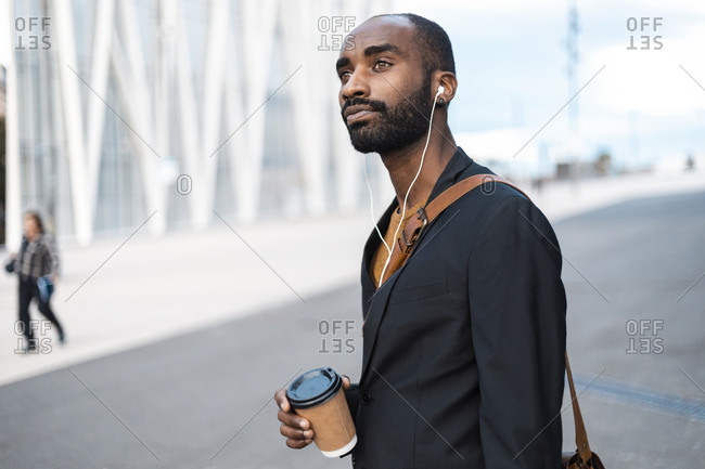 Portrait of young businessman with coffee to go listening music with earphones outdoors