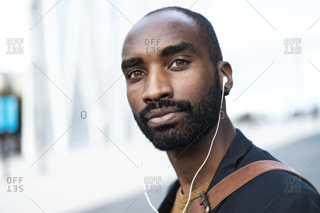 Portrait of bearded young businessman using earphones