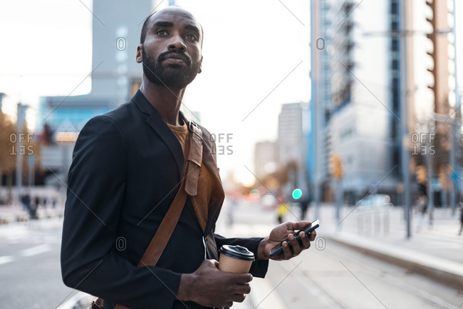 Portrait of young businessman with coffee to go and smartphone looking at distance