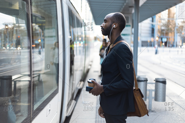 Young businessman with coffee to go standing at tram stop listening music with earphones and smartphone