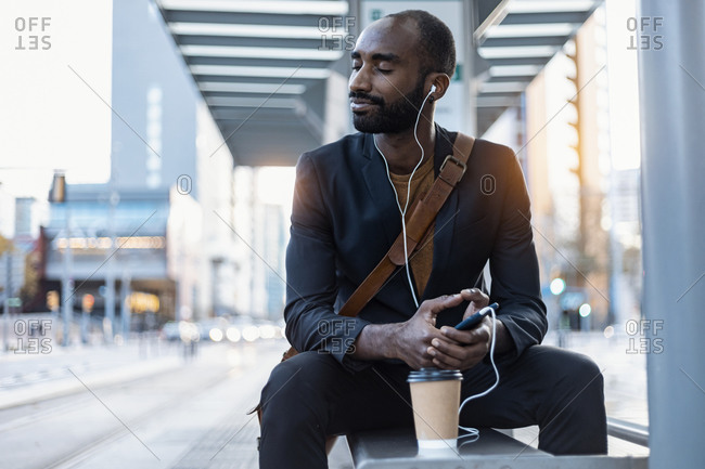 Young businessman with coffee to go listening music with earphones and smartphone relaxing at tram stop