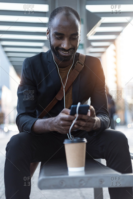 Smiling young businessman sitting at tram stop using earphones and smartphone