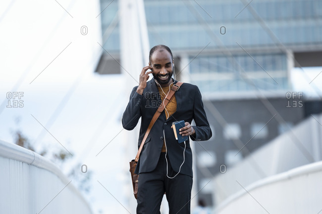 Smiling young businessman using smartphone and earphones outdoors