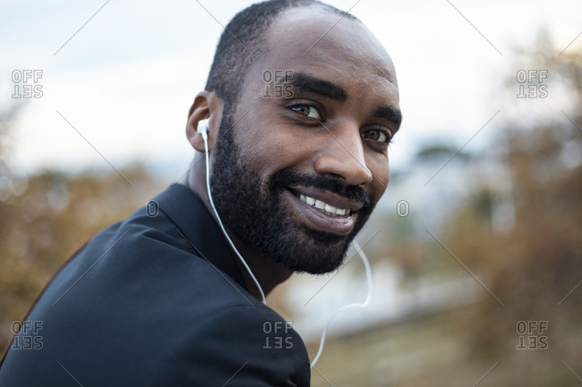 Portrait of smiling young businessman with earphones outdoors