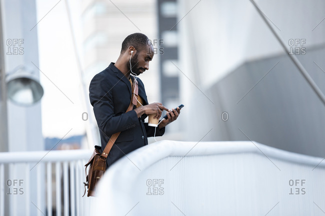 Young businessman with earphones and coffee to go using smartphone outdoors