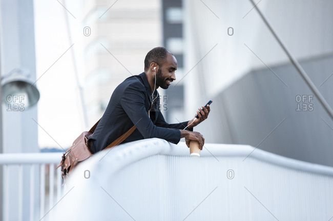 Smiling young businessman with earphones and coffee to go looking at smartphone