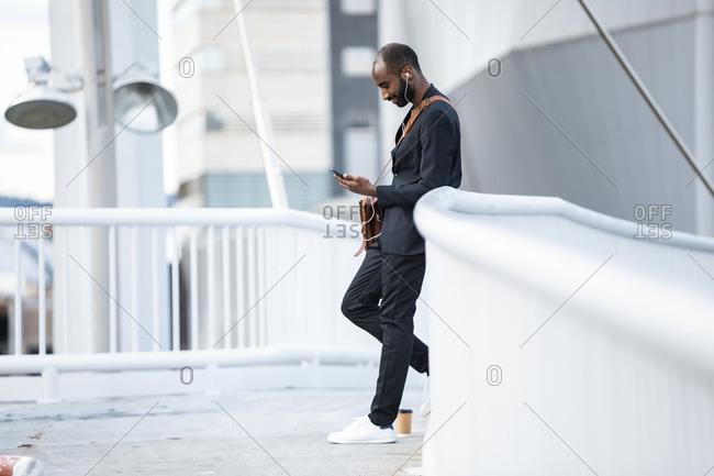 Young businessman with earphones standing on footbridge looking at smartphone