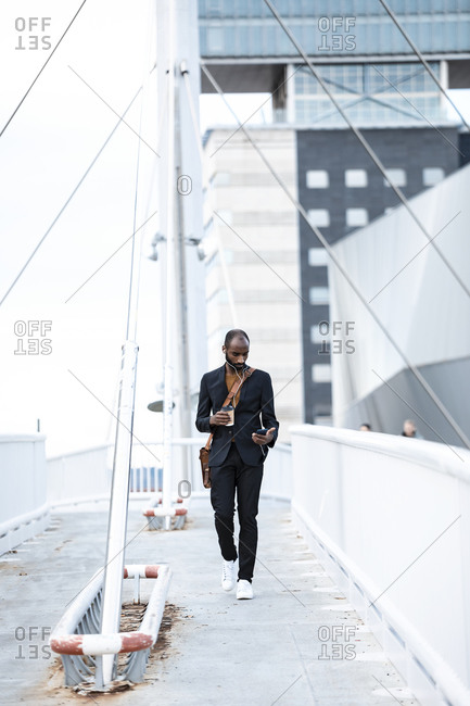 Young businessman with earphones and coffee to go walking on footbridge while looking at smartphone
