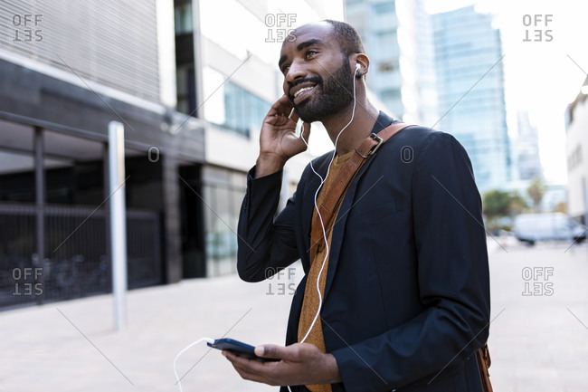 Smiling young businessman listening music with earphones and smartphone  in the city