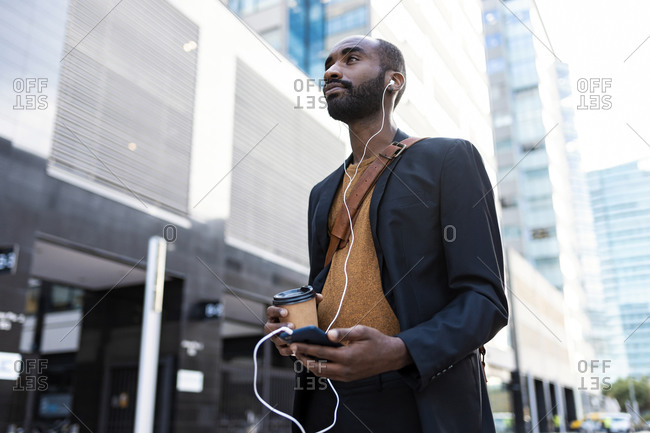 Young businessman with coffee to go listening music with earphones and smartphone in the city
