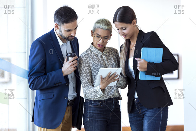Business people sharing tablet in office