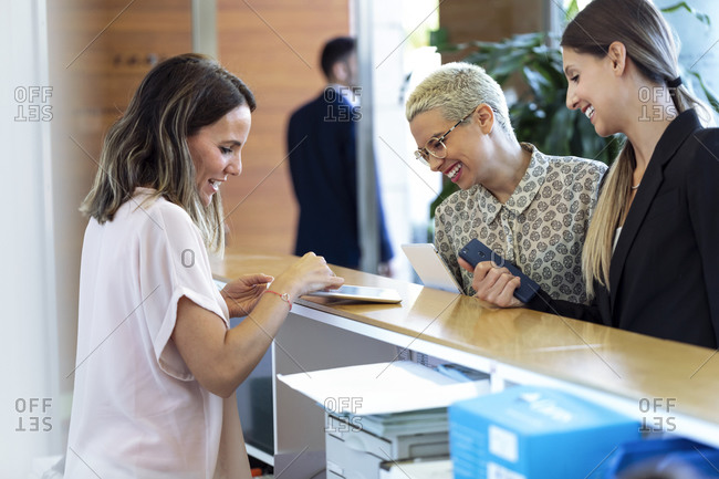 Two smiling businesswomen talking to woman at reception desk