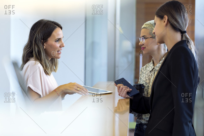 Two businesswomen talking to woman at reception desk
