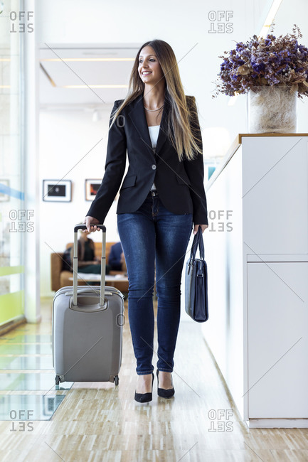 Smiling businesswomen with baggage at reception desk