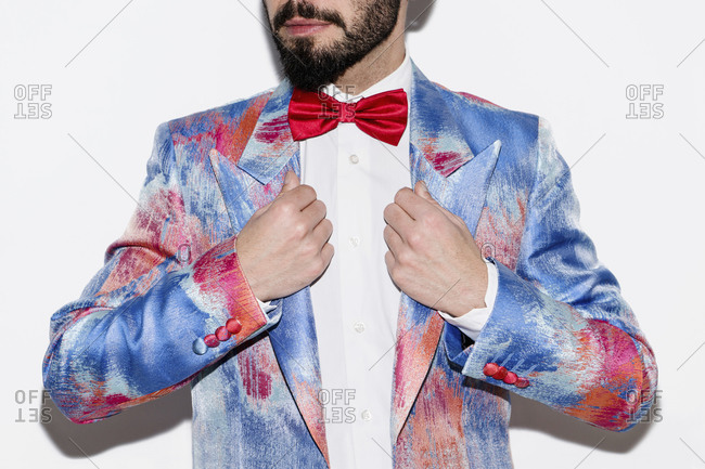 Stylish man wearing a colorful suit and a red bow tie