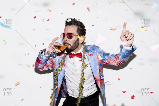 Cool and stylish man wearing a colorful suit and sunglasses celebrating a party with confetti and drinking