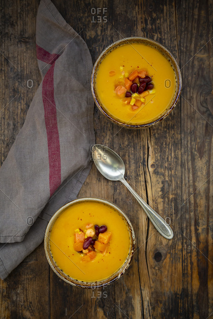 Two bowls of pumpkin-sweet potato soup with corn and kidney beans