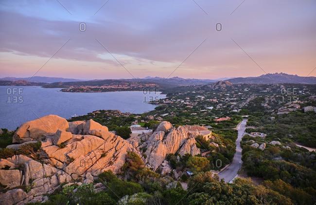 Italy- Rocks and bushes along coastline of Mediterranean Sea at dusk