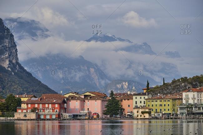 Italy- Trentino- Nago-Torbole- Coastal town on shore of Lake Garda with mountains in background