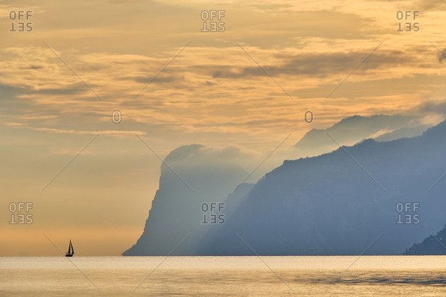 Italy- Trentino- Nago-Torbole- Silhouette of sailboat sailing near coastal cliffs of Lake Garda at moody dawn