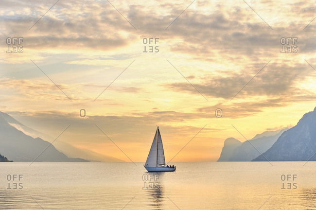 Italy- Trentino- Nago-Torbole- Sailboat sailing near coastal cliffs of Lake Garda at moody dawn
