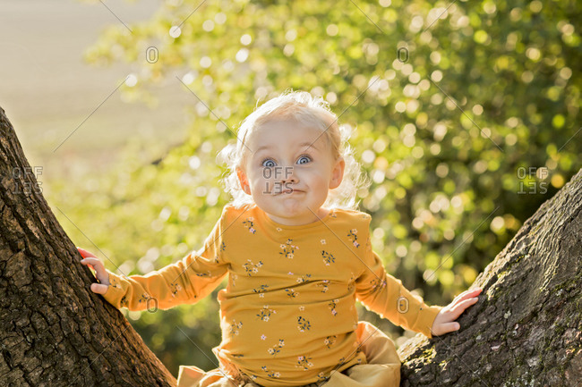 Portrait of blond toddler girl sitting on tree trunk pulling funny faces