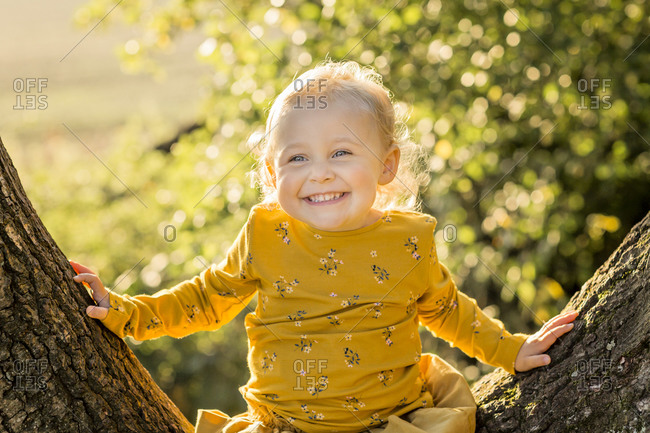 Portrait of happy blond toddler girl sitting on tree trunk