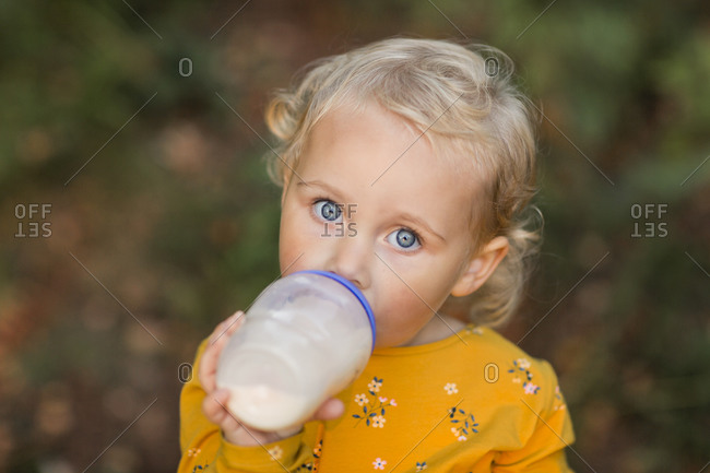 Portrait of blond toddler girl with blue eyes drinking milk from a bottle