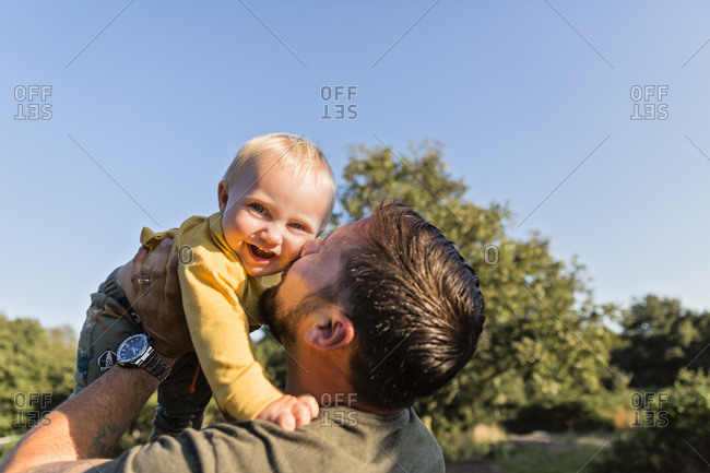 Father kissing his little son