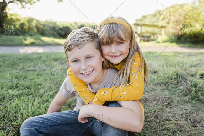 Portrait of smiling little girl head to head with her older brother on a meadow