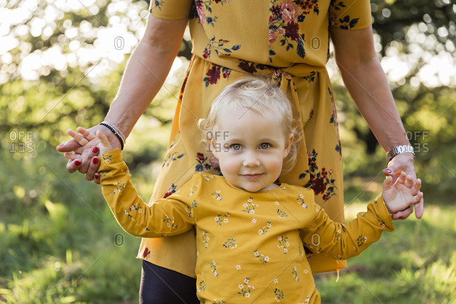 Portrait of little blond girl hand in hand with her mother on a meadow