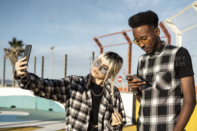 Young woman taking selfie with her boyfriend looking at his smartphone