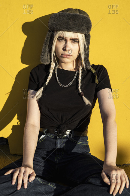 Portrait of young woman with blond braids wearing cap sitting in front of  yellow wall