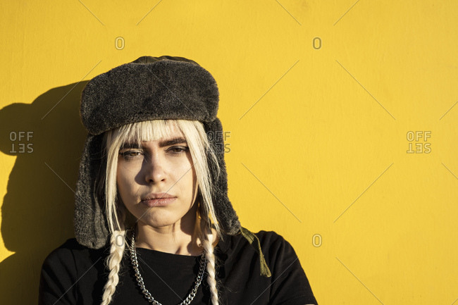 Portrait of young woman with blond braids wearing cap against yellow wall