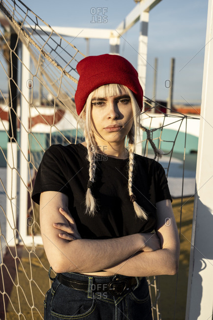 Portrait of young woman with blond braids wearing red woolly hat