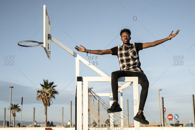 Portrait of young man sitting on soccer goal against sky