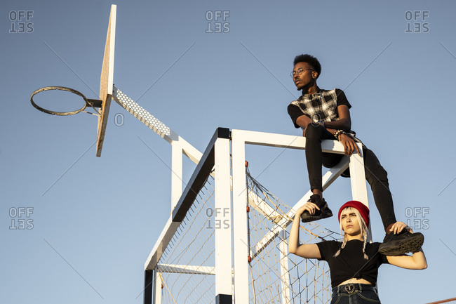 Young couple sitting at soccer goal against sky