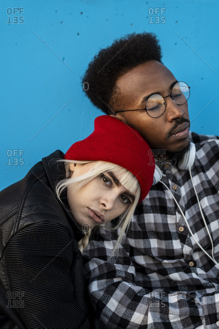 Portrait of young couple against blue wall