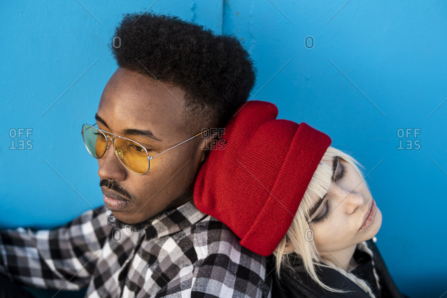 Portrait of young couple back to back against blue background