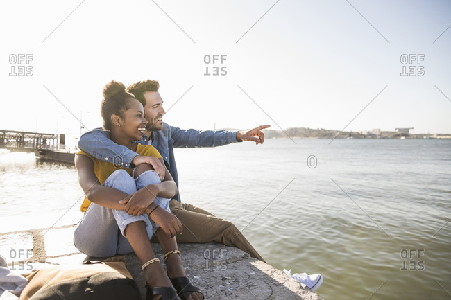 Happy young couple sitting on pier at the waterfront looking at view- Lisbon- Portugal