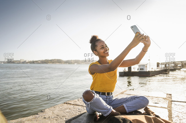 Happy young woman sitting on pier at the waterfront taking a selfie- Lisbon- Portugal