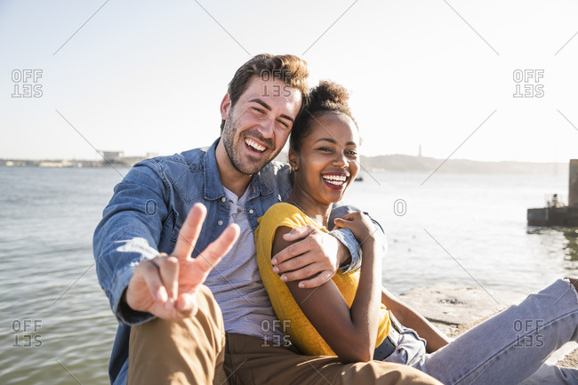 Portrait of happy young couple sitting at the waterfront gesturing- Lisbon- Portugal