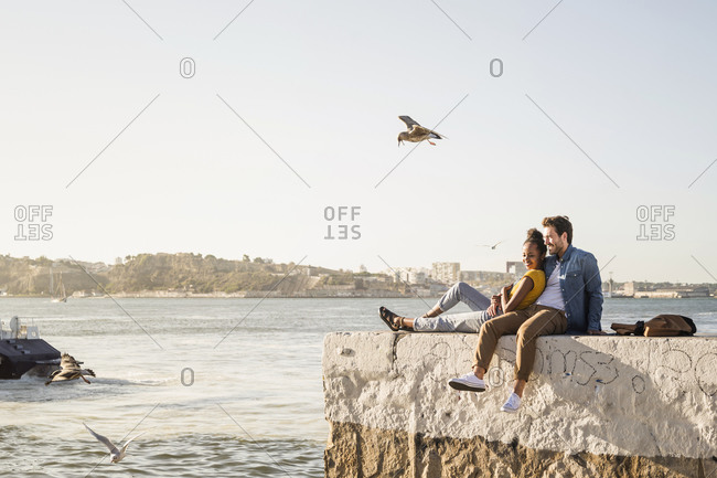 Young couple sitting on pier at the waterfront enjoying the view- Lisbon- Portugal