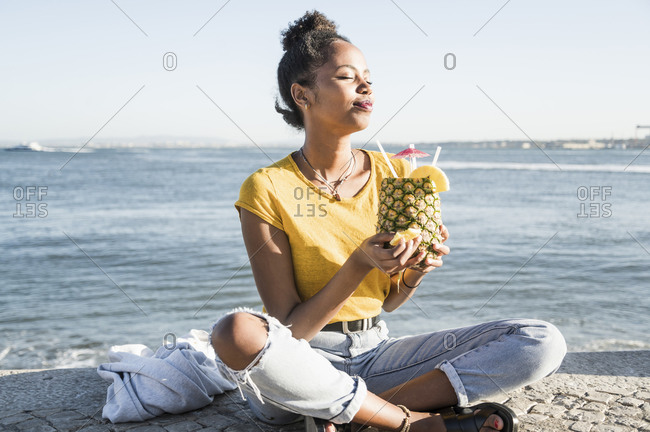 Young woman sitting at the waterfront enjoying a drink in a pineapple- Lisbon- Portugal