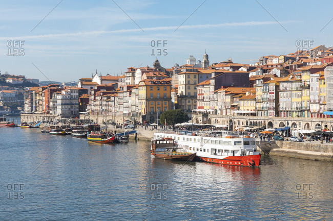 February 19, 2019: Portugal- Porto District- Porto- Boats moored along Douro river with city buildings in background